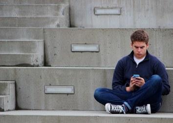 Jongere met smartphone (vergrote weergave)