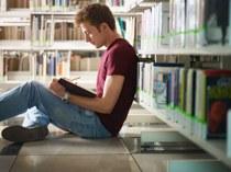 Student tussen bibliotheekrekken